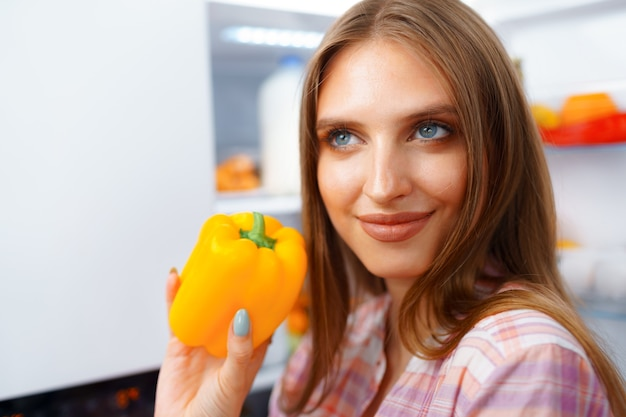 Portrait of a young blonde woman taking food from her fridge