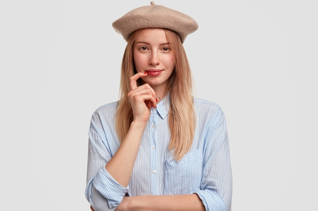 Portrait of young blonde woman wearing beret