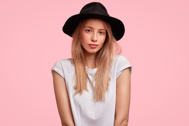 Portrait of young blonde woman wearing big hat