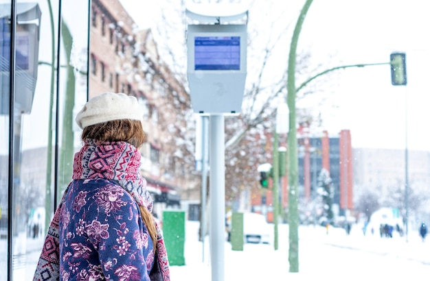 Portrait of a young blonde woman in winter clothes sitting at the bus stop. snow in the city.