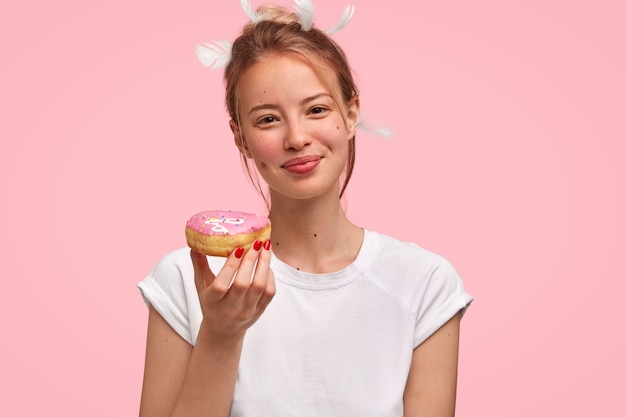 Portrait of young blonde woman with donut in hand