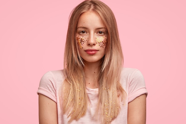 Portrait of young blonde woman with glitter on face