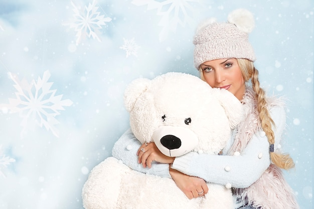 Portrait of a young blonde woman with long hair in winter clothes in an embrace with a large polar bear.