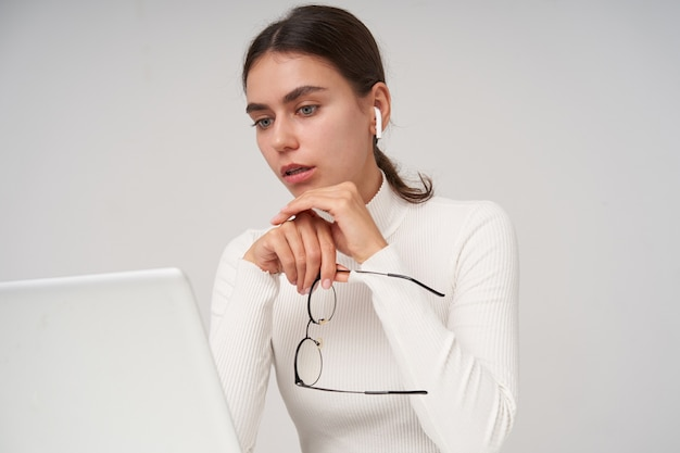 Portrait of young blue-eyed brunette woman with ponytail hairstyle looking at screen of her laptop with confused face, keeping eyewear while posing over white wall