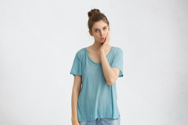 Portrait of young blue eyed female with dark hair tied in bun, wearing loose blue shirt and jeans, keeping hand on cheek, looking with serious expression, isolated.