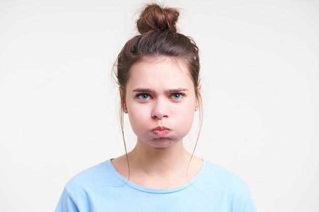 Ritratto di giovane femmina bella mora dagli occhi azzurri prendendo aria in bocca e gonfiando le guance mentre guarda davanti, in piedi sopra il muro bianco