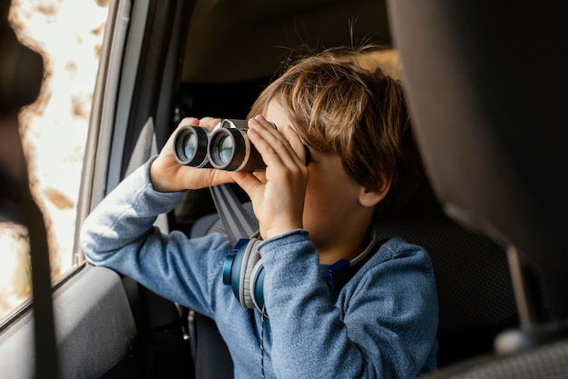Portrait young boy in car with binoculars