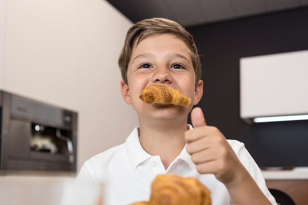 Portrait of young boy eating croissants
