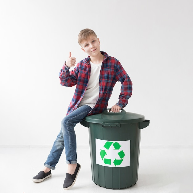 Portrait of young boy happy to recycle