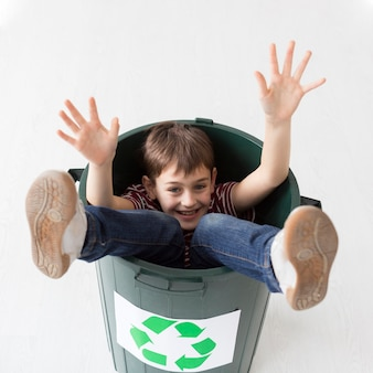 Portrait of young boy posing inside of recycle bin
