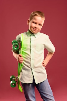 Portrait of young boy posing with skateboard