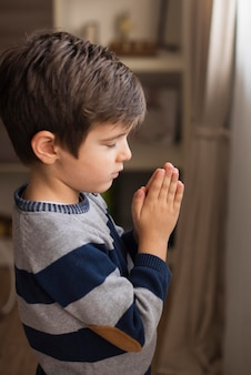 Portrait of young boy praying