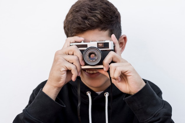 Portrait of young boy taking picture through retro camera on white backdrop