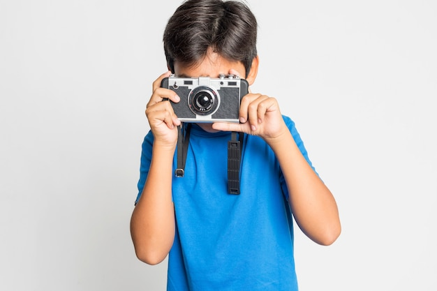 Portrait of a young boy with camera isolated on white