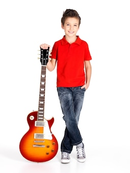 Portrait of young boy with electric guitar - isolated on white wall
