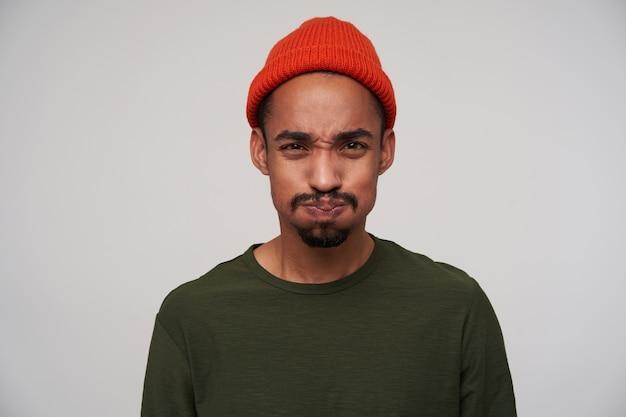 Ritratto di giovane uomo dalla pelle scura barbuto dagli occhi marroni prendendo aria nella sua bocca e sbuffando le guance, in piedi su bianco