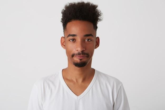 Ritratto di giovane uomo bruna dagli occhi marroni con la pelle scura mantenendo le labbra piegate