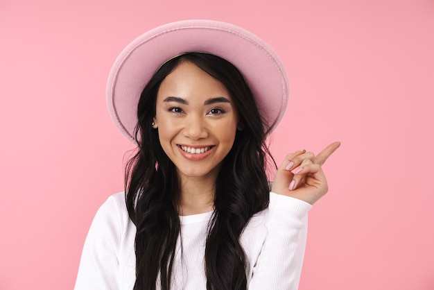 Portrait of young brunette asian woman in casual clothes pointing finger aside at copyspace isolated over pink wall