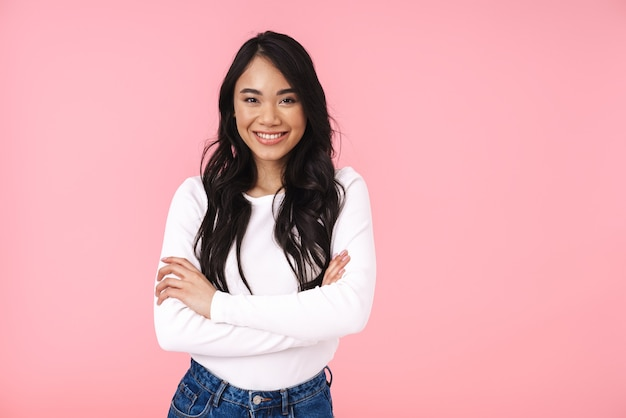 Portrait of young brunette asian woman in casual clothes standing with arms crossed and looking at camera isolated over pink wall