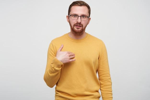 Ritratto di giovane ragazzo barbuto bruna in maglione senape con gli occhiali mentre posa, guardando confuso e indicando se stesso con il palmo sollevato