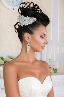 Portrait of young brunette bride with beautiful wedding coiffure