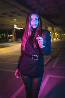Portrait of young brunette caucasian girl at night in an underground parking lot, illuminated with neon