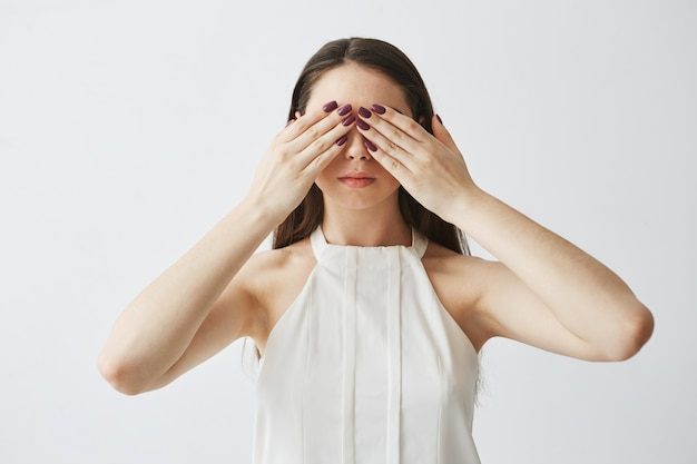 Portrait of young brunette girl covering eyes with hands .