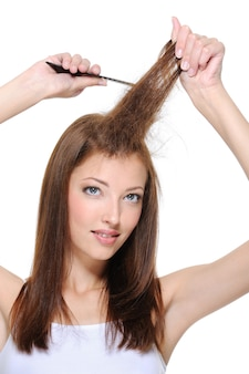 Portrait of young brunette girl doing backcombing with comb