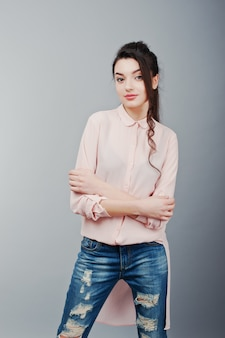 Portrait of young brunette girl wearing in pink blouse, ripped jeans