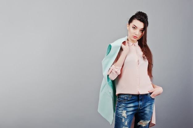 Portrait of young brunette girl wearing in pink blouse, turquoise jacket, ripped jeans