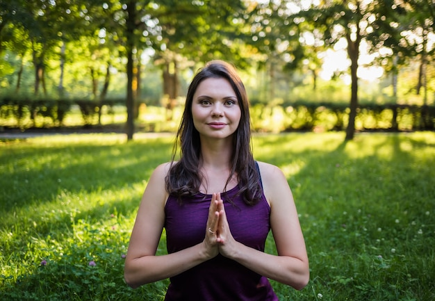 Portrait of a young brunette girl with folded hands namaste in nature at sunset