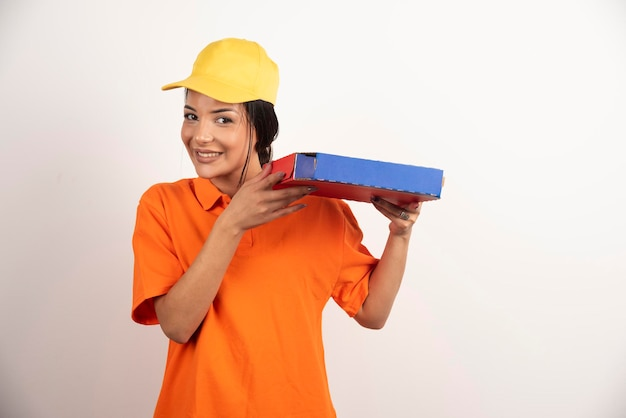 Ritratto di giovane ragazza castana con pizza in scatola sulla parete bianca.