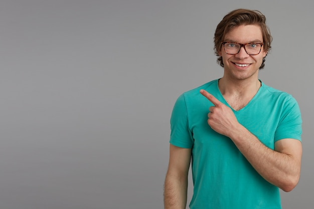 Portrait of young brunette male, isolated over gray background, wears blue t-shirt and point with a finger aside.