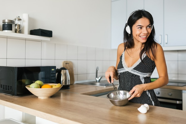 Portrait of young brunette pretty woman cooking scrambled eggs in kitchen in morning, smiling, happy mood, positive housewife, healthy lifestyle