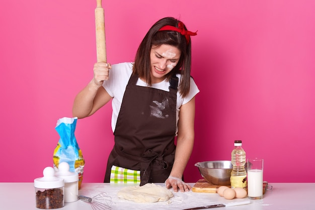 Portrait of young brunette stressed female working in kitchen whole day, preparing homemade pastry, looks tired. beats on dough with wooden rolling pin with anger isolated on rose.