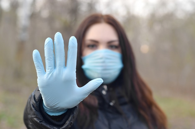 Portrait of young brunette woman in blue protective mask and rubber gloves shows stop gesture outdoors in spring wood
