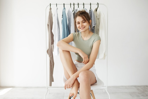 Portrait of young brunette woman smiling sitting on chair over hanger wardrobe and white wall.