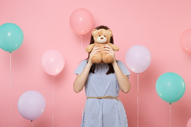 Portrait of young brunette woman wearing blue dress covering face with teddy bear plush toy on pink background with colorful air balloons. birthday holiday party, people sincere emotions concept.