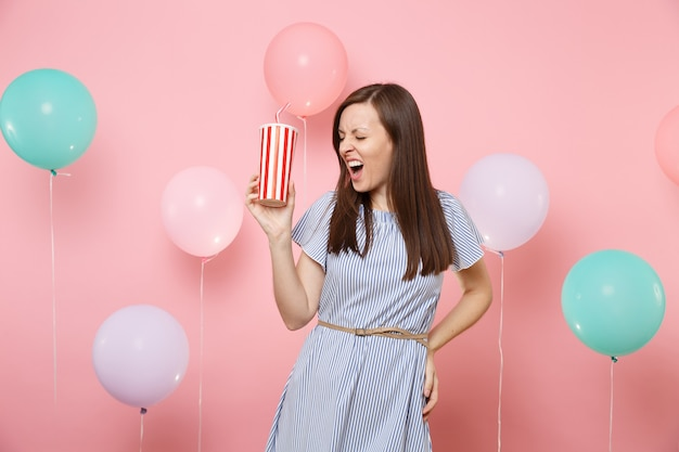 Portrait of young brunette woman wearing blue dress with closed eyes screaming holding plastic cup of cola or soda on pastel pink background with colorful air balloons. birthday holiday party concept.
