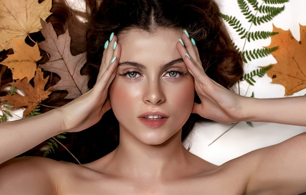 Portrait of a young brunette woman on a white background with a green fern and yellow leaves around her head, skin and hair care concept