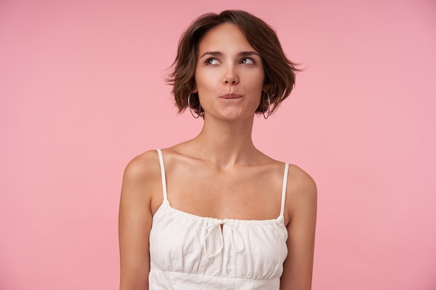 Portrait of young brunette woman with casual hairstyle looking aside cunningly, biting underlip while plotting something, wearing white top while standing