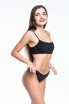 Ritratto di una giovane donna bruna con un corpo perfetto in lingerie sportiva nera in posa e guardando lontano isolato su un muro bianco