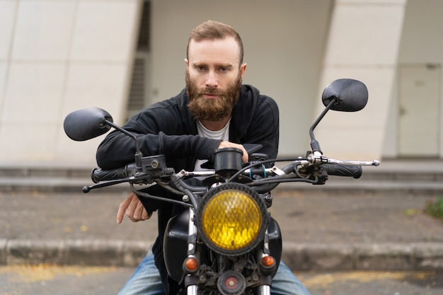 Portrait of young brutal man sitting on motorcycle outdoors