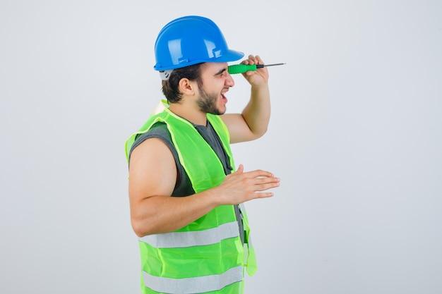 Ritratto di giovane uomo costruttore fingendo di sbirciare un buco con un cacciavite in uniforme e guardando vista frontale focalizzata