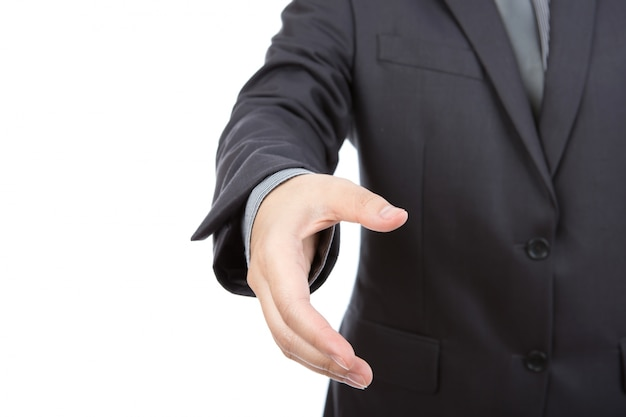 Portrait of young business man extending hand to shake against w