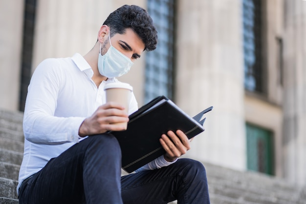 Portrait of young business man wearing face mask and reading files while sitting on stairs outdoors. business concept. new normal lifestyle concept.