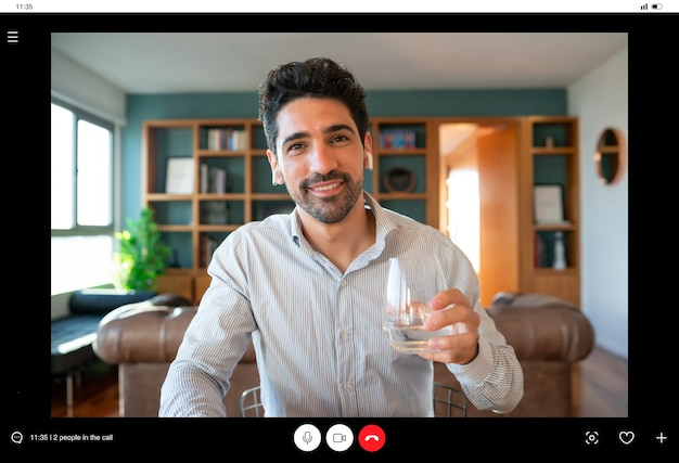 Portrait of young business man on a work video call and holding a cup of wine while staying at home