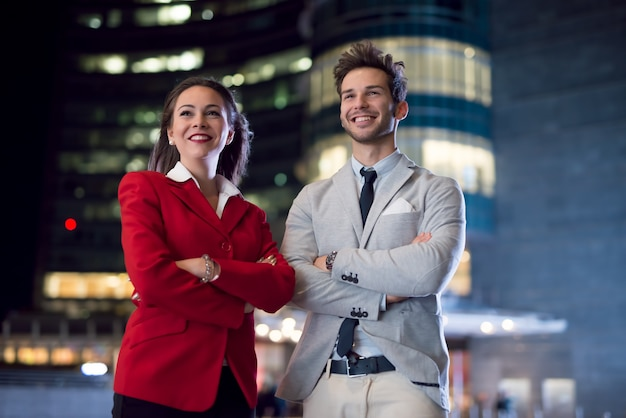Portrait of young business people at night. businessman and businesswoman together