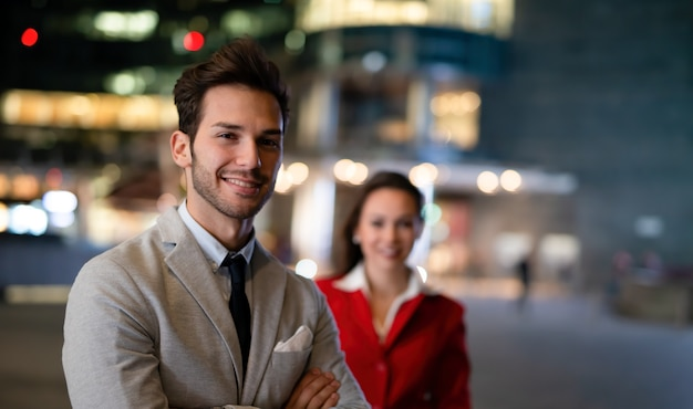 Portrait of young business people at night, businessman and businesswoman together