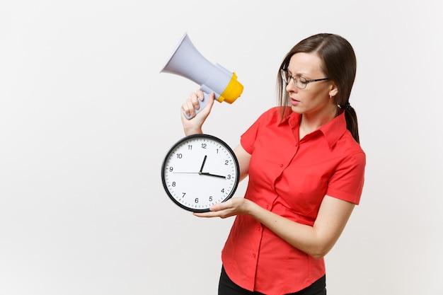 Portrait of young business teacher woman in red shirt holding round clock, scream in megaphone, announces discounts sale, isolated on white background. hot news, communication concept.. hurry up, guys